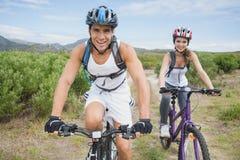 Ciclismo di montagna atletico delle coppie fotografia stock