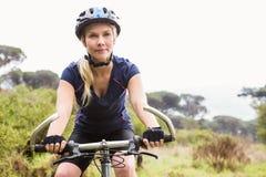 Ciclismo di montagna biondo atletico messo a fuoco Immagini Stock Libere da Diritti