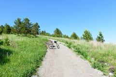 Ciclismo di montagna su una strada della montagna un giorno di estate soleggiato fotografia stock libera da diritti