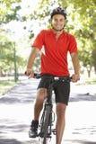 Ciclismo do homem através do parque Fotos de Stock