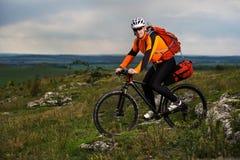 Ciclismo do homem novo em uma estrada rural através do prado verde Imagens de Stock
