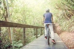 Ciclismo do homem novo na fuga da floresta durante o fim de semana Imagens de Stock