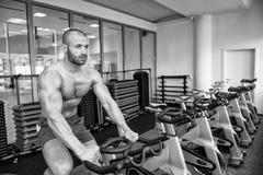 Ciclismo do homem novo no instrutor do halterofilismo da bicicleta Fotografia de Stock