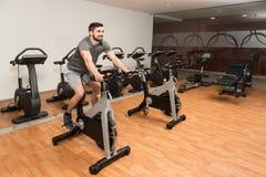 Ciclismo do homem novo no instrutor do halterofilismo da bicicleta Foto de Stock