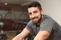 Ciclismo do homem novo no instrutor do halterofilismo da bicicleta Foto de Stock Royalty Free