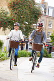 Ciclismo dos pares através do parque urbano junto Foto de Stock Royalty Free