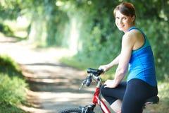 Ciclismo envelhecido meio da mulher ao longo da estrada secundária Imagens de Stock