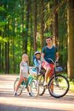 Ciclismo felice della famiglia all'aperto al parco Fotografie Stock Libere da Diritti