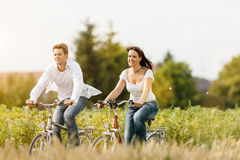 Ciclismo novo dos pares com a bicicleta no verão Imagem de Stock Royalty Free