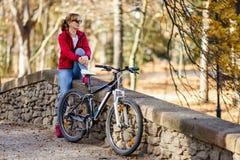Ciclismo urbano - bici di guida della donna nel parco della città Immagine Stock