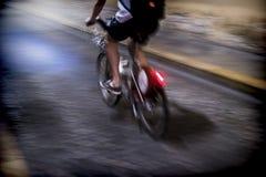 Ciclista abajo de la calle en la noche Imagen de archivo