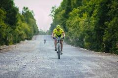 Ciclista abajo del camino de la grava Imagenes de archivo