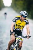 Ciclista abajo del camino de la grava Imágenes de archivo libres de regalías