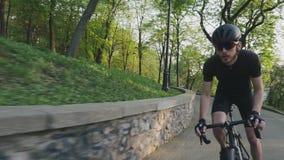 Ciclista apto fuerte enfocado que monta cuesta arriba nuestro de la silla de montar que lleva la ropa de deportes, los vidrios y  almacen de metraje de vídeo