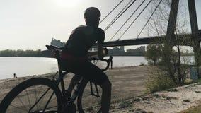 Ciclista atlético apto fuerte que se sienta en la bici que mira lejos a continuación Ciclista que sueña sobre futuro r lento almacen de video