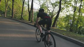 Ciclista atlético magro que desce na bicicleta da estrada no parque Ciclista que veste o equipamento preto que monta a bicicleta  filme