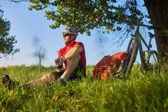 Ciclista atractivo en el casco que se sienta en el prado verde cerca del ciclo en el campo Imagen de archivo libre de regalías