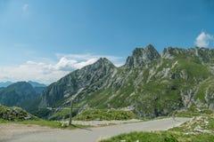 Ciclista in bella strada verde della montagna ad estate Fotografia Stock Libera da Diritti