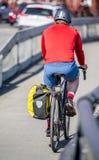 Ciclista in bici di giri degli abiti sportivi e del casco lungo il pedone e la pista ciclabile fotografia stock
