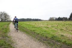 Ciclista a campo través en una trayectoria en el campo, visión trasera Imagenes de archivo