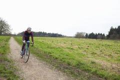 Ciclista a campo través que monta abajo de una trayectoria en campo abierto Fotos de archivo libres de regalías