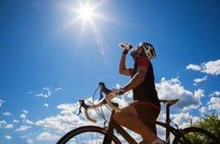 Ciclista che riposa e che beve bevanda isotonica Fotografia Stock Libera da Diritti