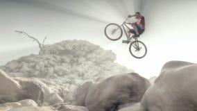 Ciclista che scala su una roccia Fotografie Stock