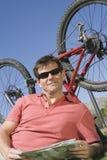Ciclista com o mapa rodoviário que encontra-se em Front Of Bicycle Upside Down Fotos de Stock Royalty Free