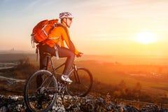 Ciclista com o Mountain bike na parte superior observando a vista No por do sol com alargamento da lente Fotografia de Stock Royalty Free