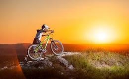 Ciclista con il mountain bike sulla collina nella sera fotografia stock
