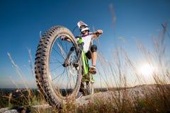 Ciclista con la bici de montaña en la colina debajo del cielo azul Fotografía de archivo libre de regalías