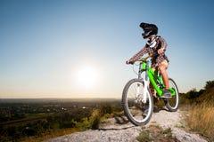 Ciclista con la bici de montaña en la colina debajo del cielo azul Imagen de archivo libre de regalías