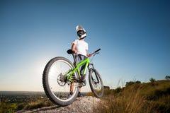 Ciclista con la bici de montaña en la colina debajo del cielo azul Imagenes de archivo