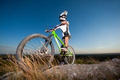 Ciclista con la bici de montaña en la colina debajo del cielo azul Fotografía de archivo