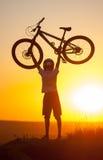 Ciclista con la bici de montaña en la colina por la tarde Fotos de archivo
