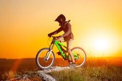 Ciclista con la bici de montaña en la colina por la tarde Fotografía de archivo libre de regalías