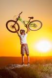 Ciclista con la bici de montaña en la colina por la tarde Fotos de archivo libres de regalías