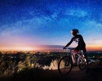 Ciclista con la bici de montaña encima de la colina fotografía de archivo libre de regalías