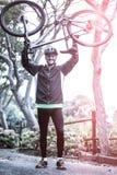 Ciclista con la bici en su cabeza Fotografía de archivo libre de regalías