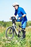 Ciclista con su bici de la bicicleta en prado Imagenes de archivo