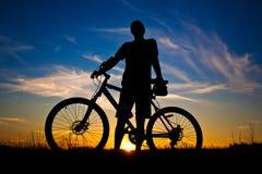 Ciclista con una silueta de la bici en un cielo azul Foto de archivo libre de regalías