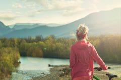 Ciclista da menina que está em uma montanha e em olhares no rio no conceito do por do sol para viajantes Vista da parte traseira  fotos de stock
