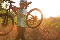Ciclista da mulher que leva seu Mountain bike Fotografia de Stock