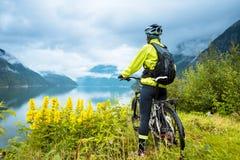 Ciclista de la bici de montaña cerca del fiordo, Noruega fotos de archivo