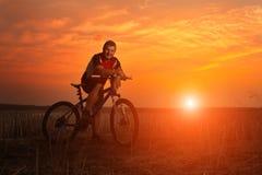 Ciclista de la bici de montaña que monta la sola pista en la salida del sol Imágenes de archivo libres de regalías