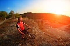 Ciclista de la bici de montaña que monta la sola pista en la salida del sol Foto de archivo libre de regalías
