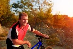 Ciclista de la bici de montaña que monta la sola pista en la salida del sol Imagen de archivo libre de regalías