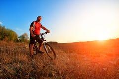 Ciclista de la bici de montaña que monta la sola pista en la salida del sol Imagen de archivo