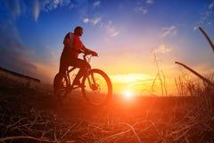 Ciclista de la bici de montaña que monta la sola pista en la salida del sol Fotografía de archivo