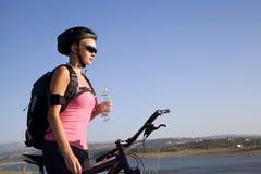 Ciclista de la mujer joven con una botella de agua Imágenes de archivo libres de regalías